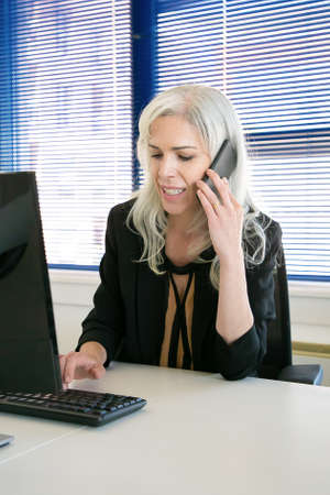 Successful grey-haired female CEO talking via cellphone and typing on key board. Content experienced beautiful businesswoman working in office room. Business, company and productivity concept