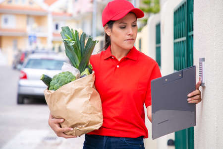 Young pretty postwoman holding paper bag and ringing doorbell. Confident brunette deliverywoman in red uniform doing her job and delivering order on foot. Food delivery service and post concept