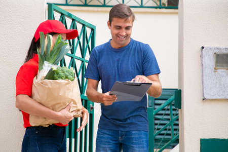 Happy man signing for receiving order from grocery store, holding clipboard and smiling. Postwoman in red uniform holding paper bag with vegetables. Food delivery service and post concept Banco de Imagens