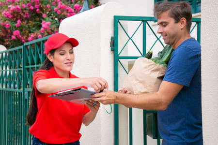 Caucasian man receiving vegetables from deliverywoman and signing in clipboard. Professional female Latin courier in red uniform delivering order from store. Food delivery service and post concept