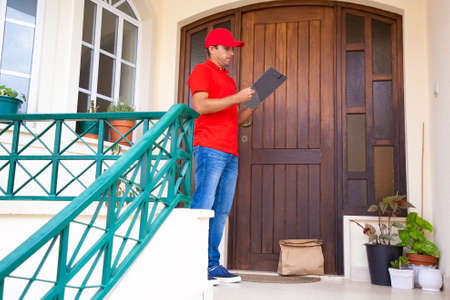 Pensive post worker standing near closed door and holding clipboard. Thoughtful courier delivering order, checking address and wearing red uniform. Delivery service and online shopping concept