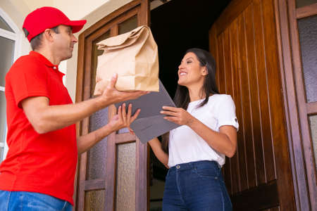 Young female receiving paper bag from courier and smiling. Caucasian deliveryman wearing red cap and shirt and giving woman clipboard for signing. Delivery service and online shopping concept Banco de Imagens