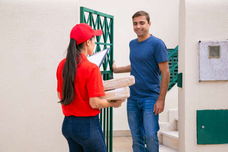 Caucasian man standing outdoors and meeting deliverywoman. Professional courier in red cap and shirt delivering parcels or boxes to clients on foot. Express delivery service and post concept 免版税图像