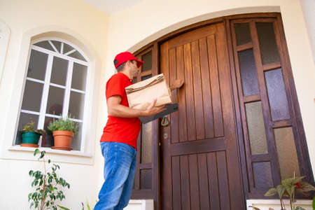 Angled view of courier knocking at door and holding paper bag and clipboard. Professional deliveryman in red cap and shirt standing in front of door. Delivery service and online shopping concept
