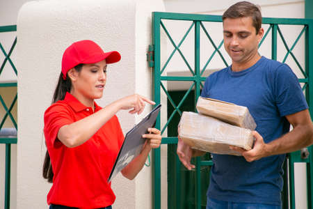 Young Latin deliverywoman standing near customer with clipboard. Handsome middle-aged Caucasian client standing on street and receiving order or cardboard boxes. Express delivery and post concept Banco de Imagens
