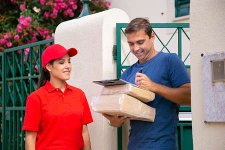 Happy man signing order sheet and holding cardboard boxes. Smiling pretty deliverywoman standing and waiting for signature from customer. Express delivery service and online shopping concept