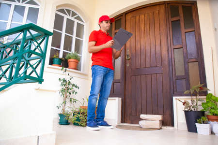 Pensive post worker standing near door and checking address. Thoughtful courier delivering order, holding clipboard and wearing red uniform. Express delivery service and online shopping concept