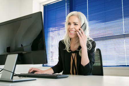Happy grey-haired businesswoman talking with colleague on phone. Professional confident manager chatting, smiling and working on computer. Business, workplace and communication concept 免版税图像