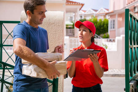 Content post office worker talking with customer and standing outdoors. Man holding cardboard boxes and listening deliverywoman with clipboard. Express delivery service and online shopping concept Banco de Imagens