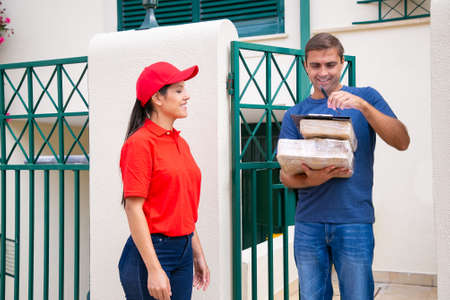 Happy postwoman waiting when client signing in clipboard, smiling and standing. Middle-aged Caucasian customer holding cardboard boxes or parcels. Delivery service and online shopping concept Banco de Imagens