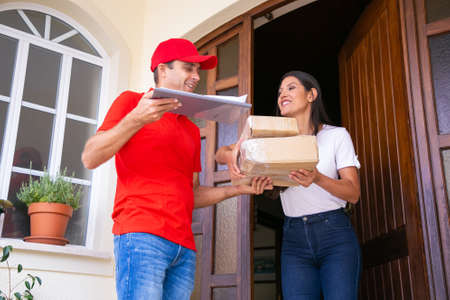 Cheerful Latin female client receiving parcels and smiling. Happy deliveryman delivering express order, talking with woman and holding clipboard. Express delivery service and post concept