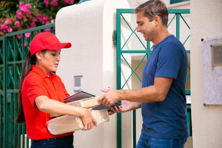 Caucasian man receiving his order from deliverywoman. Latin courier delivering order, holding parcels and clipboard, wearing red cap and shirt. Express delivery service and online shopping concept Banco de Imagens