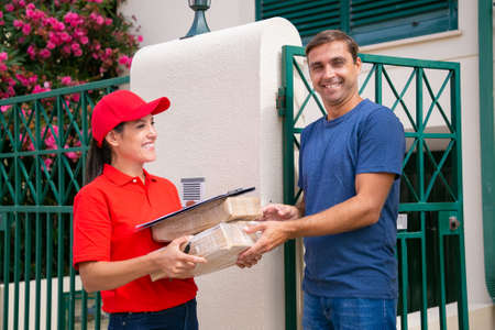 Cheerful man receiving order form deliverywoman in red uniform. Happy brunette female courier in cap delivering parcels and standing outdoors. Express delivery service and online shopping concept