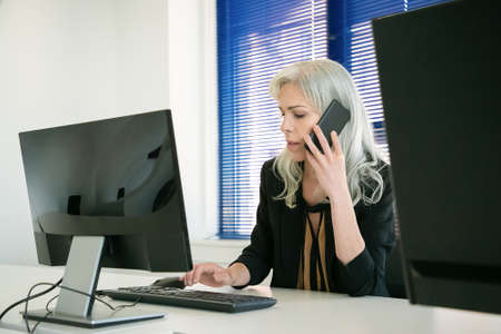 Businesswoman sitting in office and talking on phone. Grey-haired confident employee typing on computer keyboard and discussing work with client via smartphone. Business and communication concept 免版税图像