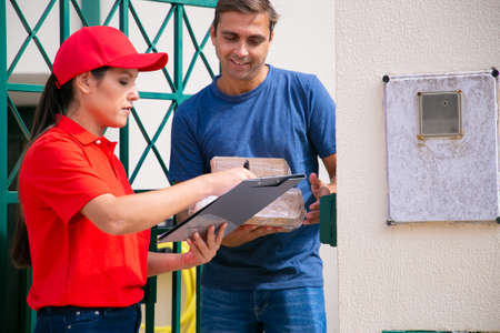 Cropped view of Latin courier delivering order to happy client. Handsome middle-aged man standing outdoors and receiving order from deliverywoman. Express delivery service and online shopping concept 免版税图像