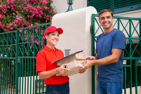 Happy male client receiving order form female courier in red uniform. Cheerful brunette deliverywoman delivering boxes and standing outdoors. Express delivery service and online shopping concept