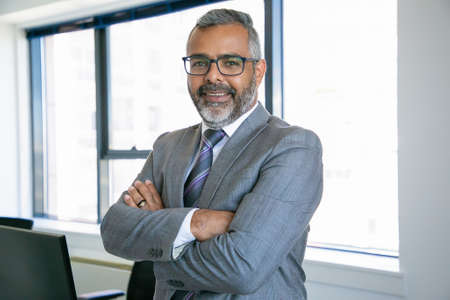 Experienced businessman standing in office room and looking at camera. Indian content office employee in eyeglasses smiling and posing with folded hands. Business, management and corporation concept 免版税图像