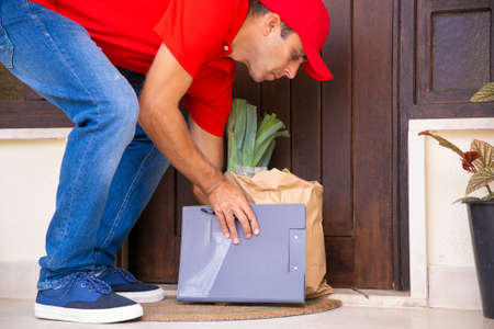 Cropped view of courier putting paper bag near door. Deliveryman delivering order from grocery store at home and wearing red shirt and cap. Food delivery service and online shopping concept 免版税图像