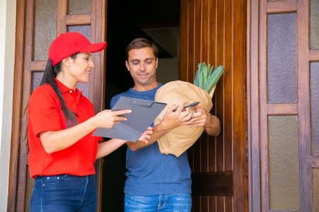 Pensive postwoman holding clipboard and showing data in order sheet. Attractive customer standing, receiving vegetables in paper bag from grocery store. Food delivery service and post concept