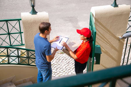 Happy female post worker delivering order to man at home. Caucasian male customer standing, receiving order and holding clipboard for signing. Express delivery service and online shopping concept