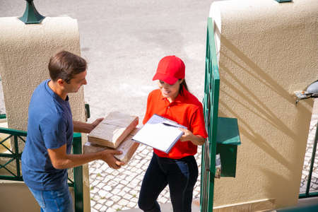 Cheerful post office worker delivering carton boxes to client, smiling and holding clipboard for signing. Attractive man receiving order at home. Express delivery service and online shopping concept