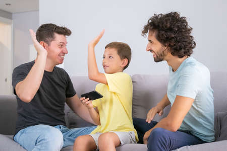 Happy boy with smartphone giving high five to two cheerful dads. Fathers and son playing game on mobile phone together. Family at home and parents concept