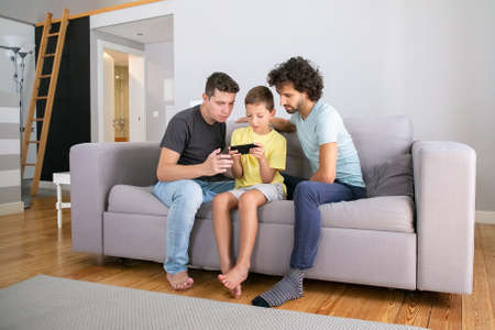 Serious boy playing online game on cellphone, his two dads sitting near him and looking at screen. Family at home and communication concept