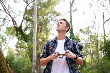 Pensive guy holding camera, looking away and choosing shoot. Caucasian backpacker exploring nature and taking photo of nature. Trees on background. Tourism, adventure and summer vacation concept