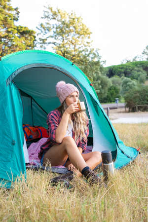 Happy blonde woman in hat drinking tea, sitting in tent and looking away. Caucasian long-haired traveler camping on lawn in park and relaxing on nature. Tourism, adventure and summer vacation concept