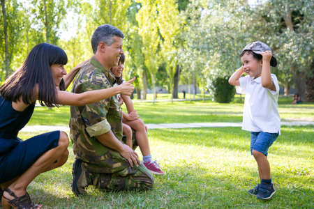Happy military father in uniform returning to family. Children with mom meeting dad, boy trying on camouflage cap. Family reunion or returning home concept