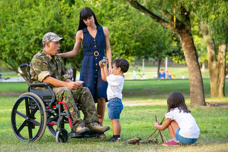 Children arranging wood for campfire in park near mom and disabled military dad in wheelchair. Boy showing log to excited father. Disabled veteran or family outdoors concept
