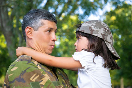 Positive dad in camouflage uniform holding offended daughter in arms, hugging girl outdoors after returning from military mission trip. Closeup shot. Family reunion or returning home concept