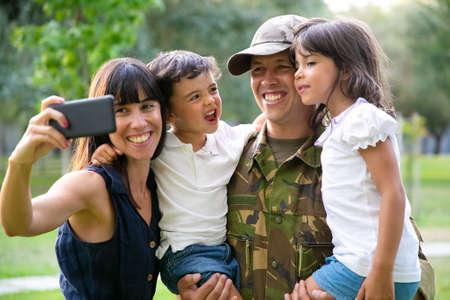 Happy joyful military family celebrating dads returning, enjoying leisure time in park, taking selfie on smartphone. Medium shot. Family reunion or returning home concept