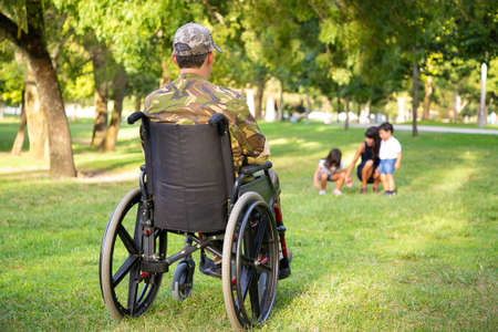 Lonely disabled retired military man in wheelchair looking at his wife and little children playing together in park. Back view. Veteran of war or disability concept