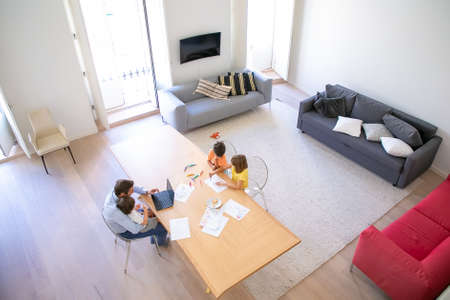 Top view of father and children sitting at table together. Two kids painting doodles with colorful pens. Middle-aged dad using laptop and holding little son. Childhood, interior and family concept