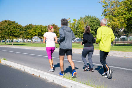 Group of mature joggers in sports clothes running outside, training for marathon, enjoying morning workout. Full length shot. Retired people and active lifestyle concept Standard-Bild