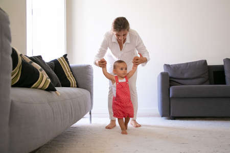 Front view of mom holding little girl hands and helping to walk. Cute barefoot baby girl in red dungarees shorts learning walking in living room with help of mother. Family time and first step concept