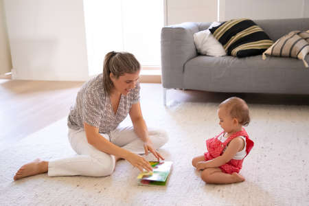 Pretty mother reading book to cute little baby in red dungarees shorts. Concentrated toddler sitting on carpet in living room and learning reading. Family, motherhood and being at home concept
