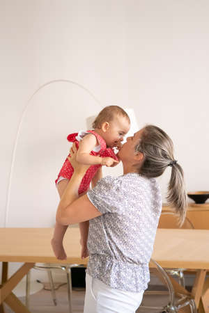 Blonde mother playing with cute baby girl, rising her up and having fun. Happy infant in red dungarees shorts looking at mom and biting finger. Family time, motherhood and being at home concept 版權商用圖片