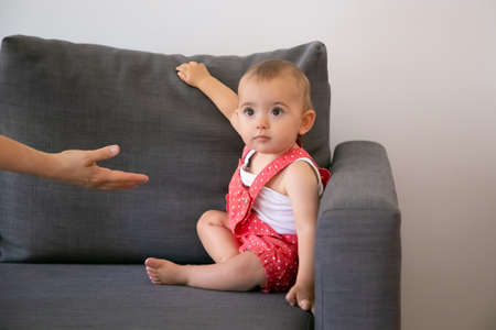Funny little baby sitting on grey sofa and looking at unrecognizable person. Someone giving hand to adorable little girl in red dungarees shorts. Family, childhood and being home concept