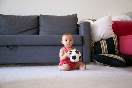 Thoughtful baby girl holding soccer ball, sitting on carpet barefoot and looking away. Lovely toddler in red dungarees shorts playing at home near sofa. Holiday, weekend and childhood concept 版權商用圖片