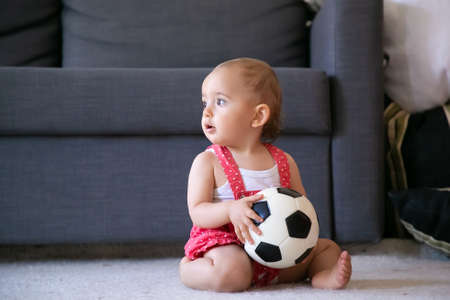 Adorable baby girl holding soccer ball, sitting on carpet barefoot and looking away. Cute infant in red dungarees shorts playing at home alone. Holiday, weekend and childhood concept 版權商用圖片