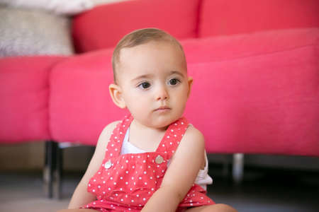 Pensive baby sitting on floor in living room and thinking about something. Serious little girl in red dungarees shorts looking away and sitting near sofa. Weekend, childhood and being at home concept 版權商用圖片
