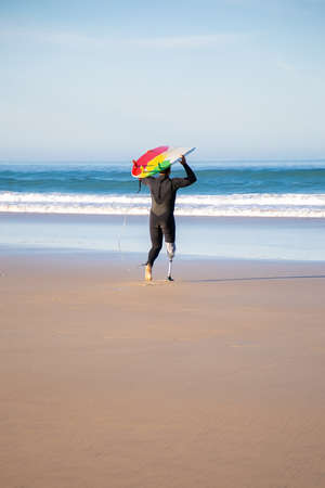 Back view of handicapped surfer going to sea with board. Active man with amputated leg holding surfboard and surfing at summer vacation. Vertical shot. Artificial limb and extreme sport concept