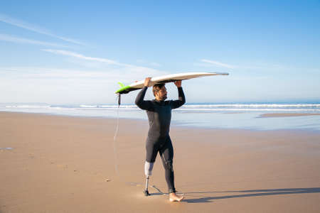 Male surfer wearing artificial limb and wetsuit, walking on beach, carrying surfboard overhead. Full length. Artificial limb and active lifestyle concept