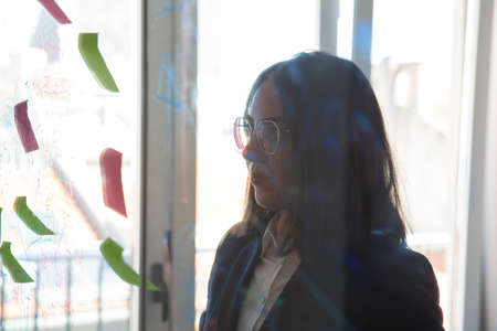 Focused female manager looking at sticky notes on glass board, analyzing project strategy and plan. View through glass. Management concept Stock Photo