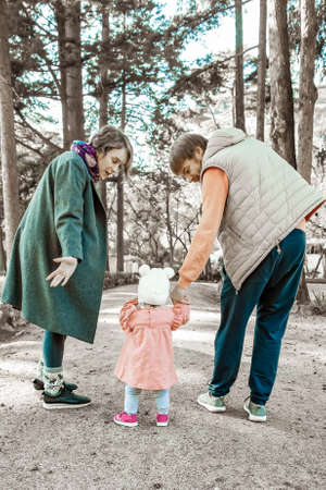 Family couple helping baby girl to walk in autumn park. Kid holding dads arm. Back view, full length. Family and childhood concept