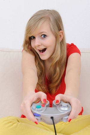 cute blond and happy girl playing playstation at home photo