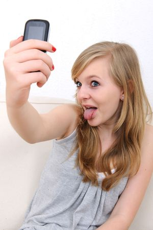 call out: girl sticks out her tongue and takes a photo with her cellphone