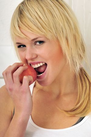 beautiful blond girl eating a red apple photo